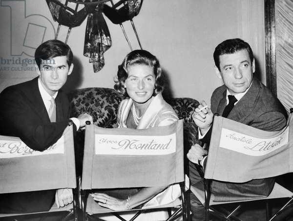 GOODBYE AGAIN, from left: Anthony Perkins, Ingrid Bergman, Yves Montand in mismatched director's chairs on set, 1961