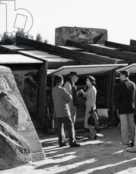 Frank Lloyd Wright (scarf) greeting Lydia Heston and Charlton Heston (back to camera right) at Taliesin West, his winter home in Arizona, 1950s