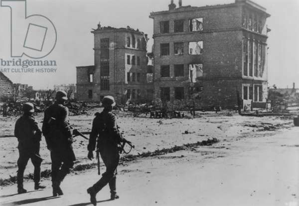 Stalingrad 1942: Three German soldiers walking in desolate street in the ruins of Stalingrad in Sept. 1942. The battle had begun on August 23, 1942, with German Luftwaffe bombing. Soviet Union (Russia), World War 2. (BSLOC_2014_8_39)