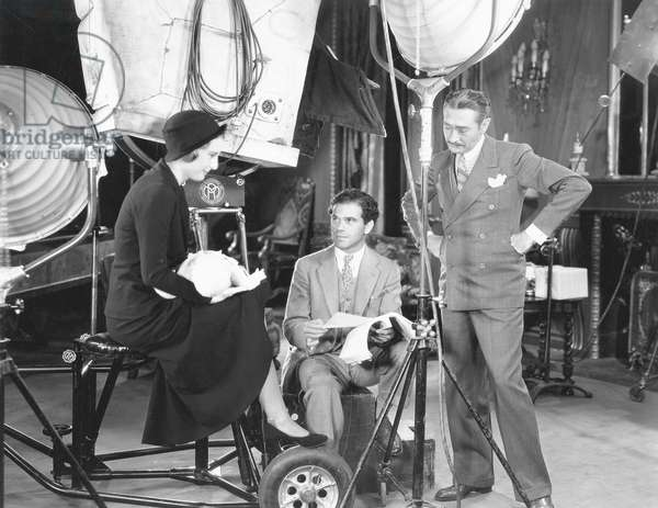 FORBIDDEN, from left: Barbara Stanwyck, director Frank Capra, Adolphe Menjou, on set, 1932