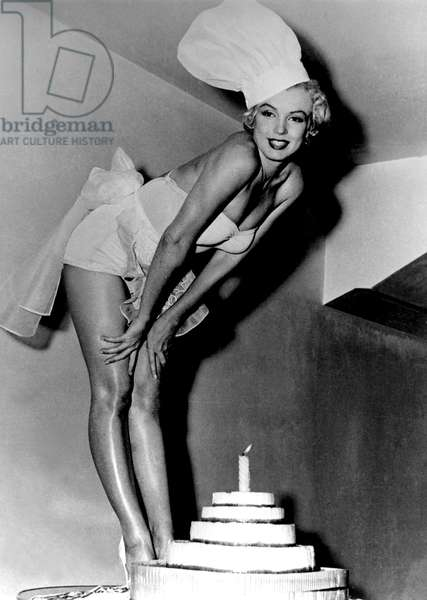 Marilyn Monroe posing in chef's hat with cake