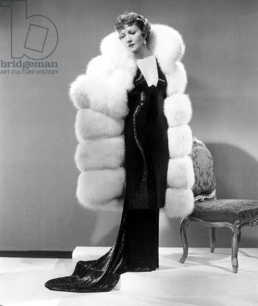 Claudette Colbert, in Travis Banton gown and white fox fur coat, 1935