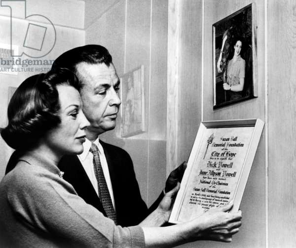 Dick Powell, wife June Allyson, hang plaque on which they are named co-chairmen of the Suzan Ball Memorial Fund, ca. late 1950s