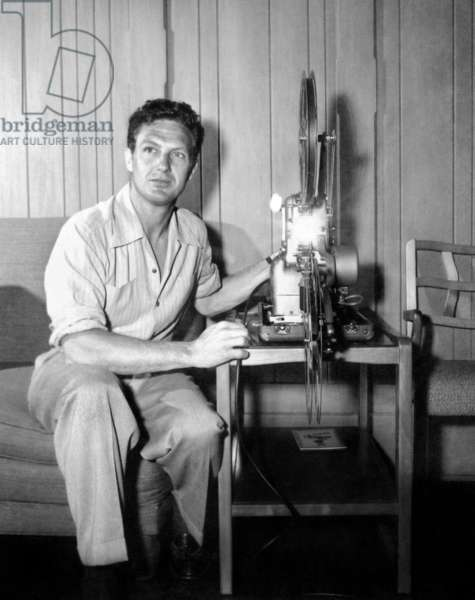 Robert Stack, with his movie projector, at home, 1954