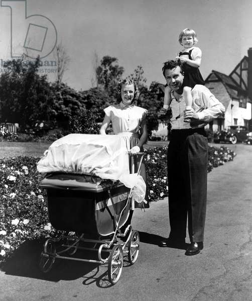 Baby DICK POWELL, JR. (in carriage) is proudly wheeled by mom JUNE ALLYSON and husband DICK POWELL (daughter PAMELA POWELL riding piggyback on dad's shoulders), 1951