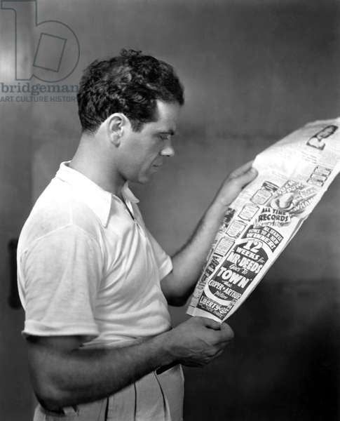 Director FRANK CAPRA reads the rave reviews and sock box office of MR. DEEDS GOES TO TOWN, 1936