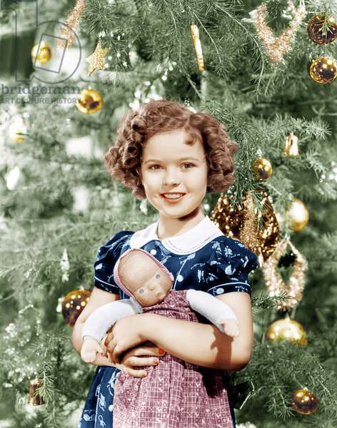 Shirley Temple holding doll by Christmas tree, ca. late 1930s