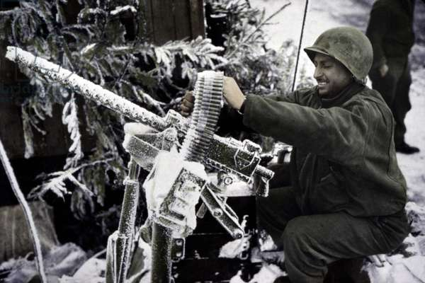 U.S. soldier checks his .30-caliber machine gun during the Battle of the Bulge. Jan. 1-20, 1945. Belgium, World War 2. B&W Photo with oil color. (JTHIS_2014_3_210)