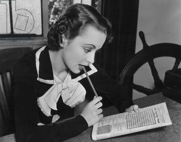 OLIVIA DE HAVILLAND working on a crossword puzzle
