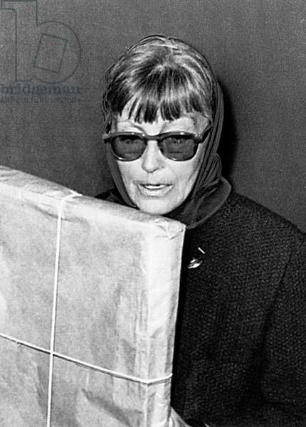 GRETA GARBO, arriving at JFK Airport, NY, hiding behind sunglasses, to avoid the photographers, 10/7/64.