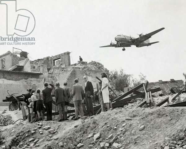 West Berliners: West Berliners gathered near war ruins in Berlin watch a U.S. Air Force transport plane. The Berlin Airlift supplied the city with food and fuel for a year during the Soviet blockade of all land routes to West Berlin from June 1948 to May 1949.
