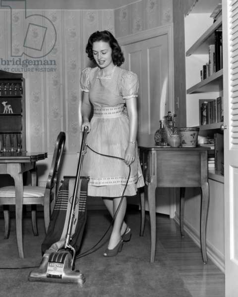 Donna Reed at home vacuuming, 1943
