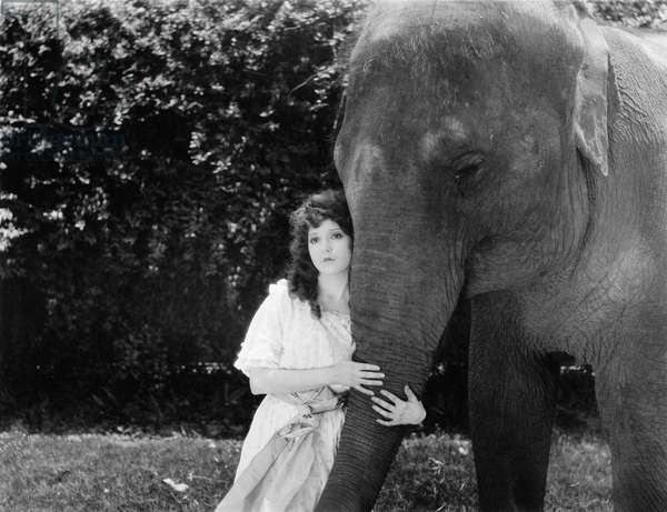 Young Woman Hugging the Trunk of an Elephant