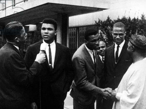 Muhammad Ali being interviewed while friend Malcolm X speaks with others in the mid 1960s