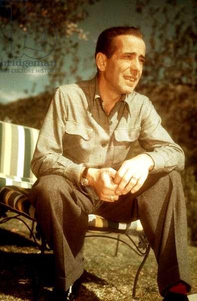 HUMPHREY BOGART, on lounge chair, enjoying leisure time in his yard, 1940s