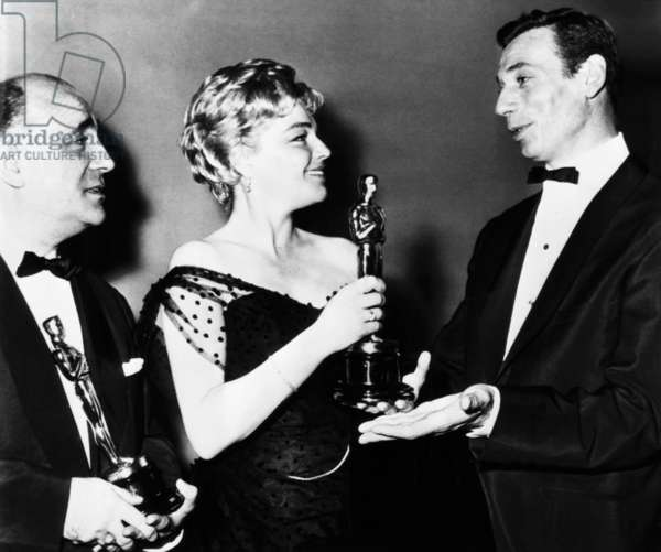 From left: Sacha Gordine accepting the Best Foreign Langauge Film Academy Award for BLACK ORPHEUS, Simore Signoret with her Best Actress Academy Award for ROOM AT THE TOP, Yves Montand, 1960