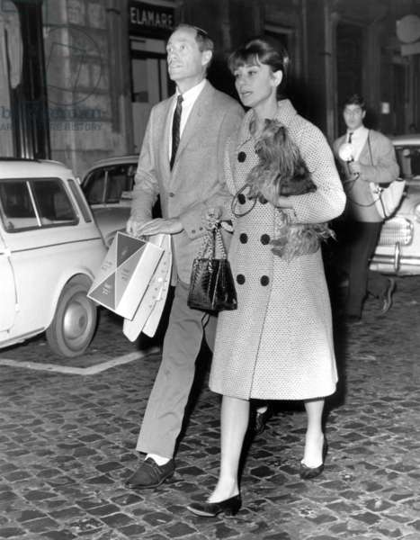Mel Ferrer and Audrey Hepburn, carrying her dog, Famous, shopping in Rome, Italy. January, 1962