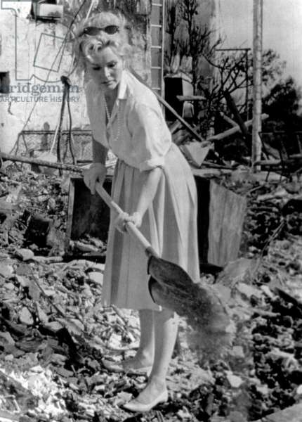 Zsa Zsa Gabor shovels through debris of her gutted home after a fire, 1961