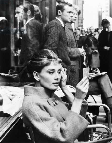 BREAKFAST AT TIFFANY'S, Audrey Hepburn examining her makeup between scenes on set, 1961: BREAKFAST AT TIFFANY'S, Audrey Hepburn examining her makeup between scenes on set, 1961