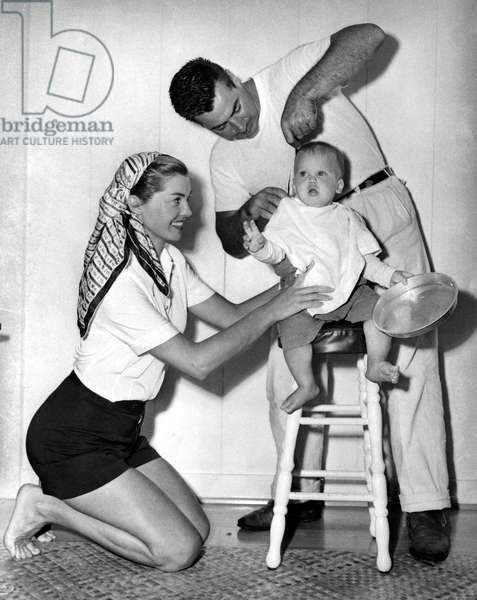 ESTHER WILLIAMS and a barber giving her 10 month old son, Benjamin, his first haircut, June 1950.