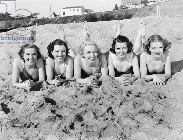 Portrait of Five Young Women Lying on the Beach and Smiling