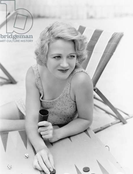 Young Woman Sitting at the Beach Playing Backgammon