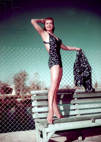 Esther Williams, in bathing suit standing on park bench, undated