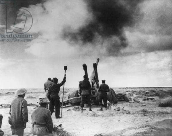 British artillery shelling an enemy position in Libya: British artillery shelling an enemy position in Libya during World War 2. Ca. 1941-42. (BSLOC_2014_10_1)