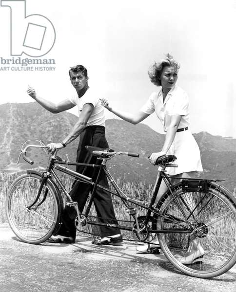 Tired of riding their tandem, newlyweds RONALD REAGAN and JANE WYMAN try to hitch a ride, 1940