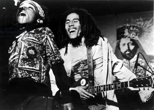Bob Marley, with son Ziggy, Haile Selassie poster at rear, 1970s.