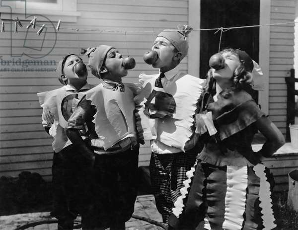 Kids Biting Apples on Strings at Halloween