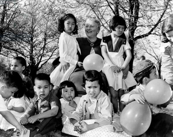 Pearl S. Buck: Pearl S. Buck (1892-1973), sits outdoors with group of Chinese-American children placed with families through her Welcome House adoption agency. Buck received Nobel Prize for Literature in 1938.