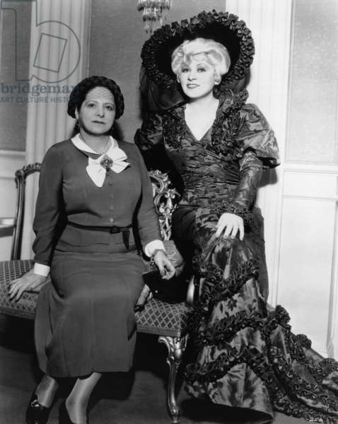 Mae West, right, with Helena Rubinstein, on the set of BELLE OF THE NINETIES, 1934