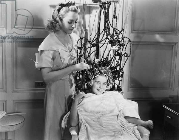 Woman Using Machine to Style Teenage Girls Hair