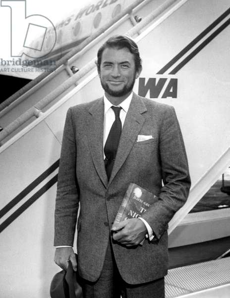 Gregory Peck in MOBY DICK beard about to board an airplane with a copy of Davis Grubb's NIGHT OF THE HUNTER, 1955