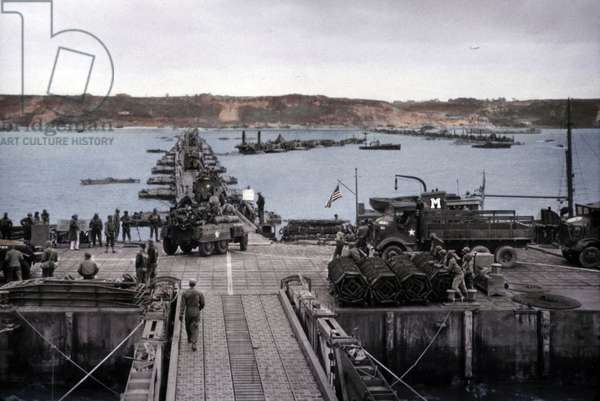 Debarquement de Normandie : Mulberry A: Artificial harbor off Omaha beach in operation before the storm on June 19-22, 1944. Vehicles move from the piers over the causeway to the Normandy shore. These floating causeways to the beach rose and fell with the tide. France, World War 2. B&W Photo with oil color. (JTHIS_2014_3_66)