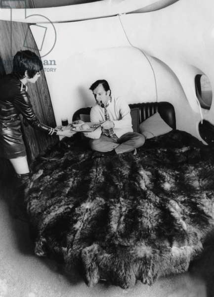 Hugh Hefner being served breakfast aboard his private plane, ca. 1966