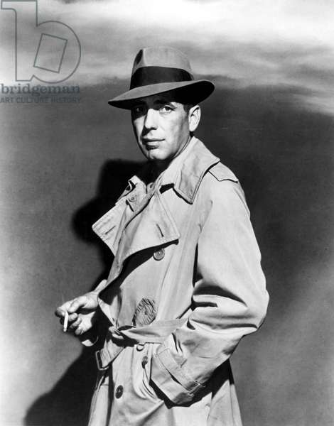 HUMPHREY BOGART, in trenchcoat, smoking a cigarette, 1940s