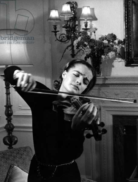 Romy Schneider, wearing Chanel, in her London hotel room practicing violin for her role in THE VICTORS, 1963