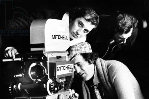 1900, director Bernardo Bertolucci looking through camera lens, on set, 1976