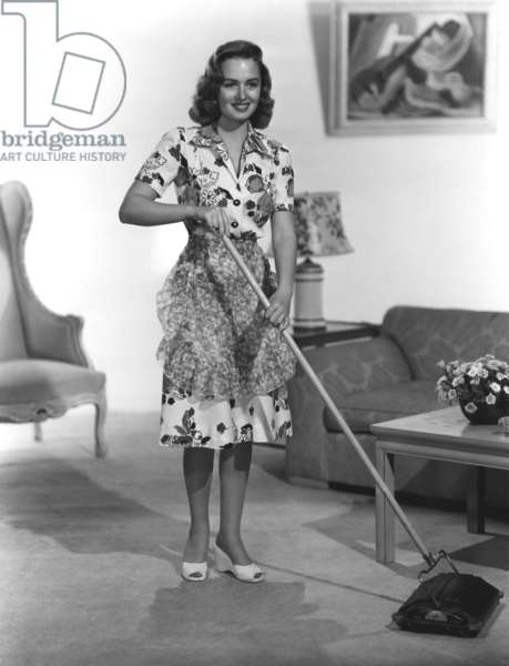 Donna Reed modeling a cotton-print dress and flowered organza apron, 1946