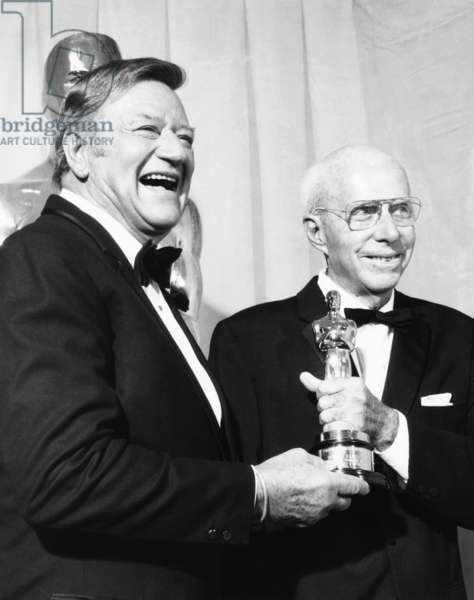 From left: John Wayne presenting an honorary Oscar to director Howard Hawks, 47th Academy Awards, April 8, 1975