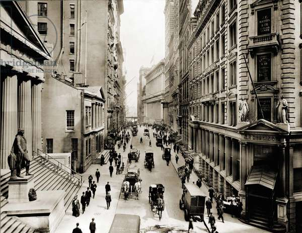 Wall Street: New York City's Wall Street, looking east from the intersection with Broad Street. In foreground left is Federal Hall; on right is J.P. Morgan's bank. Horse drawn vehicles make deliveries. Photo by Irving Underhill, Ca. 1910.
