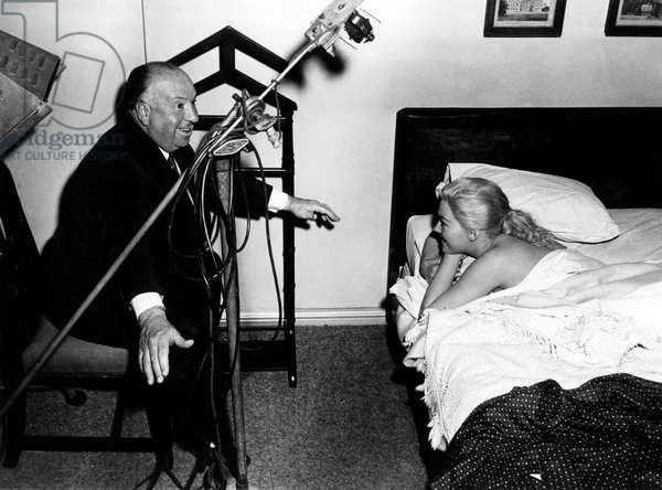 VERTIGO, Director Alfred Hitchcock directs Kim Novak on set, 1958