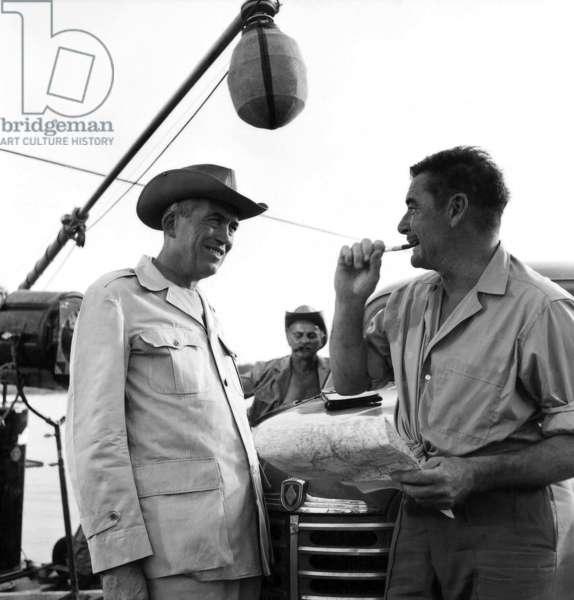 John Huston et Errol Flynn: THE ROOTS OF HEAVEN, director John Huston, Errol Flynn, on location, 1958, (c) 20th Century Fox, TM & Copyright / Courtesy: Everett Collection