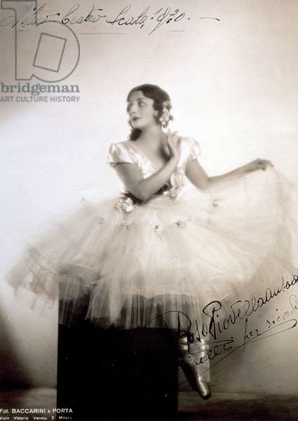 Portrait of the classical ballerina Rosa Piovella Ansaldo, in tutu and ballet shoes. She is seated, frontally, her face turned to one side. Cloth roses decorate her garment and carefully dressed hair (Milan, Teatro alla Scala) (b/w photo)