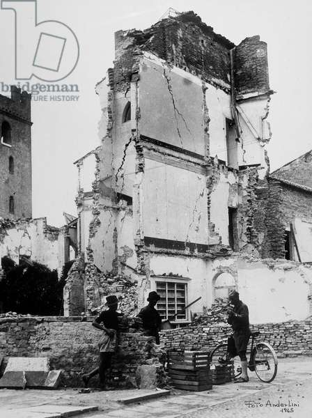 The bombardements of Sermide. Three people in front of a group of bombarded houses, 17-25/02/1945 (b/w photo)