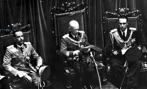 King Vittorio Emanuele III of Italy, flanked by his son Prince Umberto of Savoy and Prince Amedeo, Duke of Aosta, inaugurates the 30th legislature of the Kingdom of Italy before the Chamber of Fasci and Corporations, 23rd March 1939 (b/w photo)