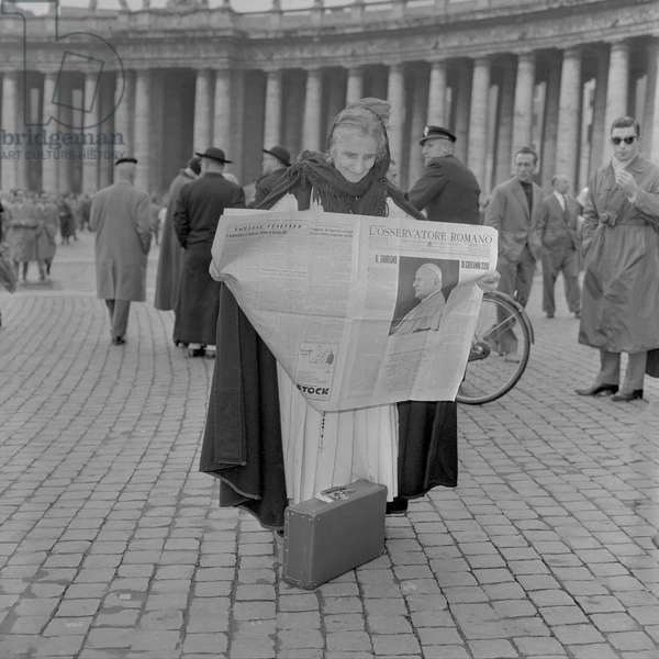 A woman reads the news of the election of Pope John XXIII, Vatican City, 4th November 1958 (b/w photo)