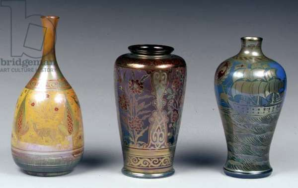 L-R: Tall-necked vase decorated in the Persian manner, 1912; high-shouldered vase decorated with panels of dog roses, c.1903, Richard Joyce (1873-1931); galleon vase with heraldic devices by William S. Mycock (1872-1950) 1914, all Pilkington Royal Lancastrian (lustreware)